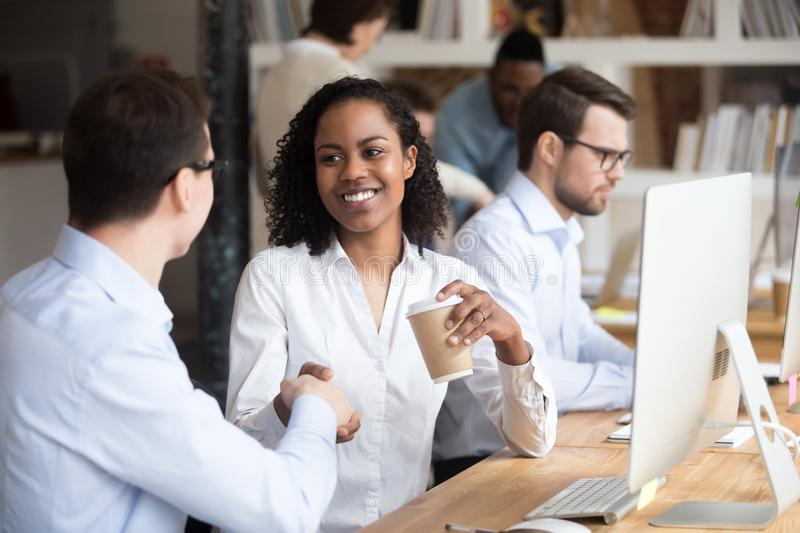 Diverse workers greeting each other shaking hands in coworking office royalty free stock photo