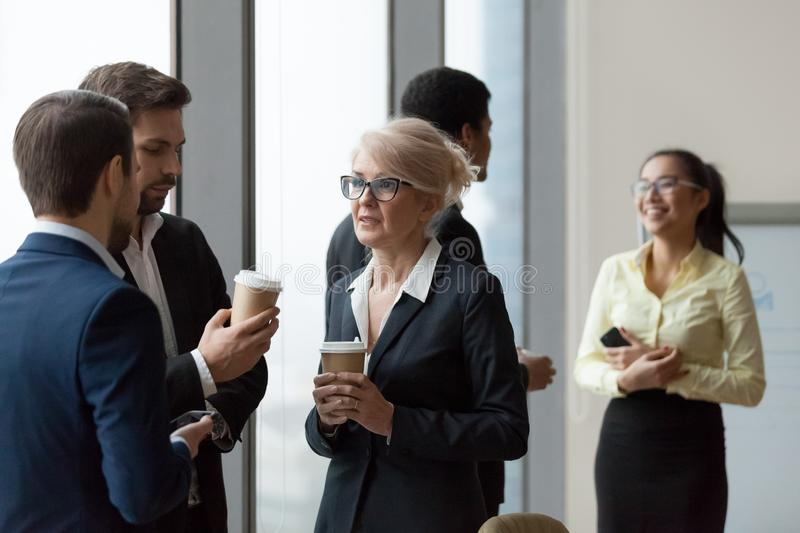 Diverse workers having conversation standing in office at work break. Friendly executives talking at work break, diverse workers having conversation standing in stock images