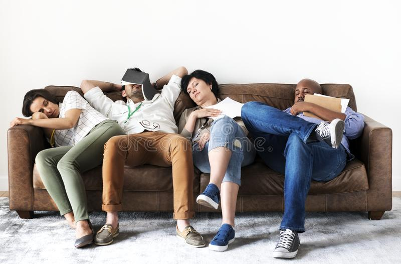 Diverse workers taking rest on couch stock images