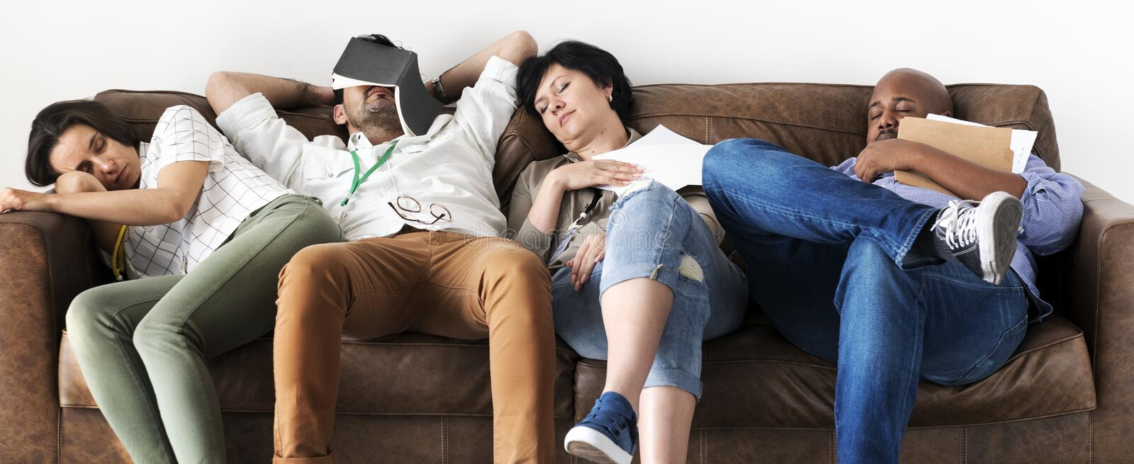 Diverse workers taking rest on couch stock photo