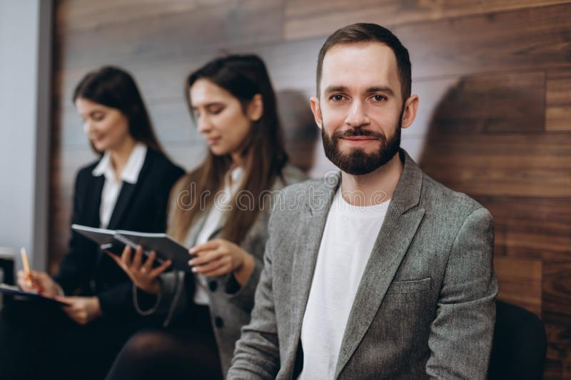 Diverse young businesspeople students friends sitting together in chairs in queue using mobile phones wait job interview or stock images