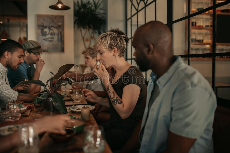 Diverse young friends enjoying a bistro meal in the evening royalty free stock image