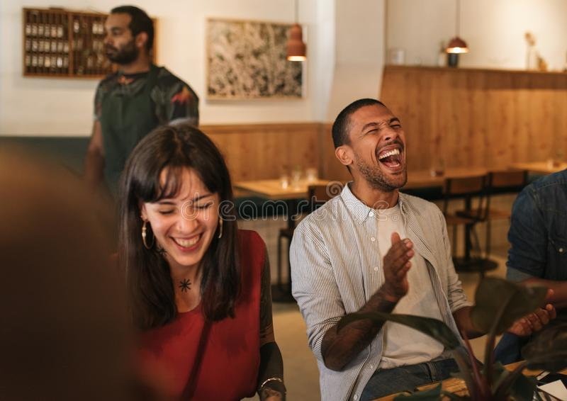 Diverse young friends laughing together during a restaurant dinner stock photo