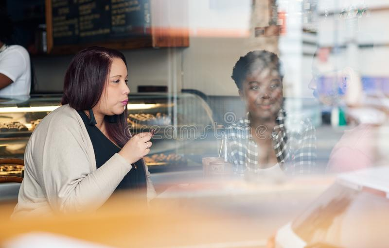 Diverse young friends talking together inside of a cafe stock photo
