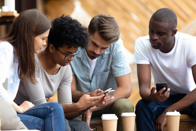 Diverse young people busy using smartphones together stock images