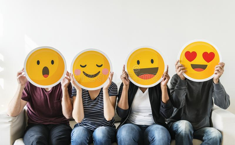 Diverse young people holding emoticon royalty free stock image