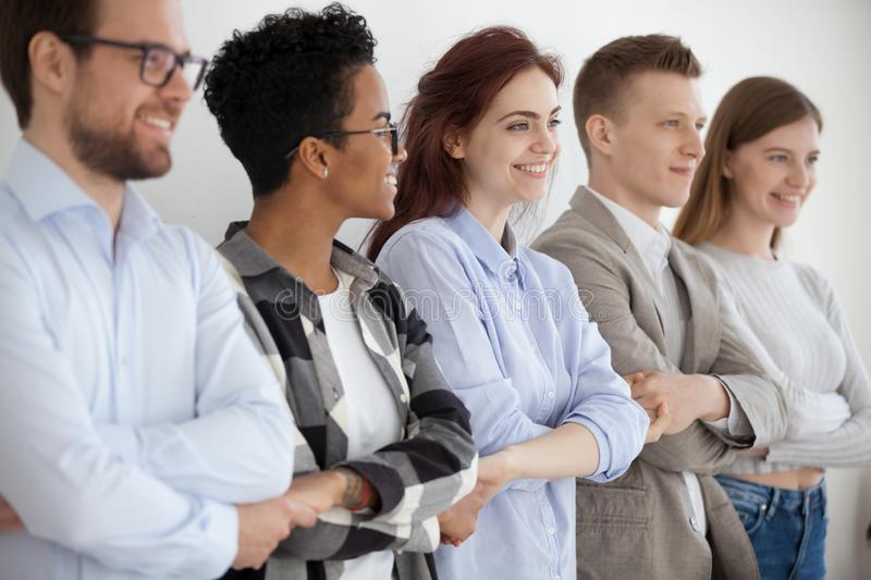 Diverse young people holding hands showing unity and teamwork. Group of diverse millennial workers standing holding hands showing unity and support, multiracial royalty free stock image