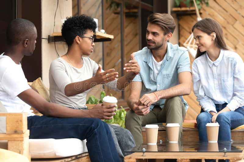 Diverse young people relax in cafe communicating royalty free stock images