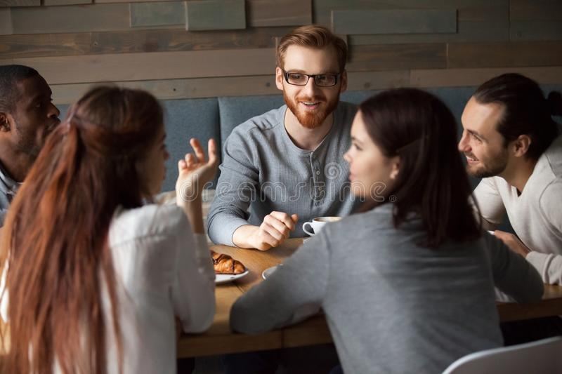 Diverse young people talking and having fun together in cafe stock photo