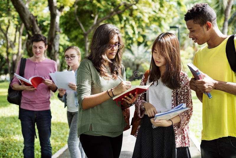 Diverse Young Students Book Outdoors Concept stock image