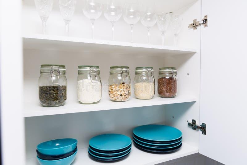 Diverse zaden in opslagkruiken in voorraadkast, witte moderne keuken op achtergrond Slimme keukenorganisatie stock foto's