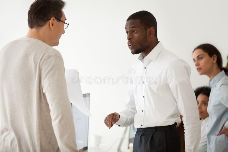 Diverse zwarte werknemer en witte werkgever die op het werk debatteren stock foto's