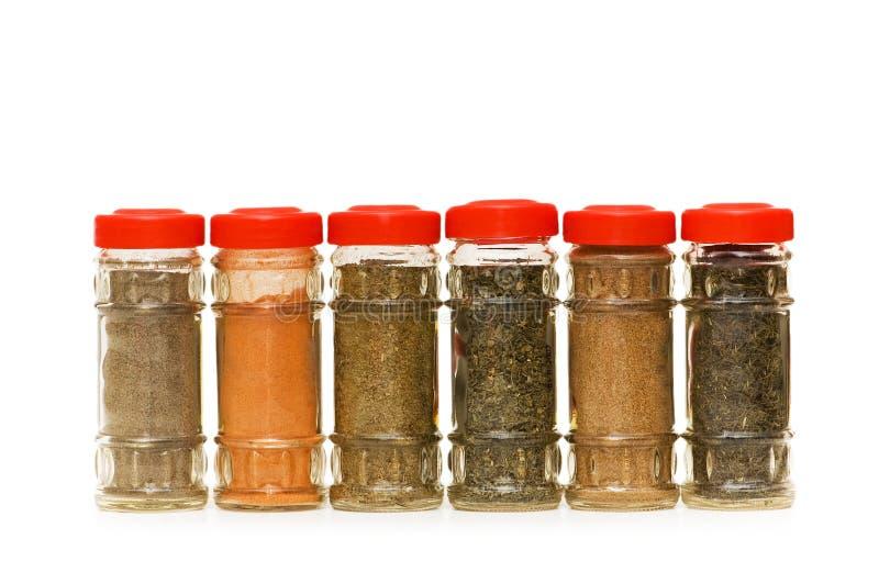 Diverses épices dans des bouteilles d'isolement photo stock