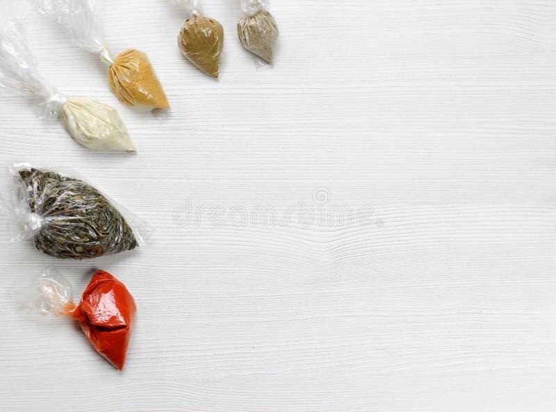 Diverses épices et herbes emballées dans de petits sachets en plastique transparents photos libres de droits
