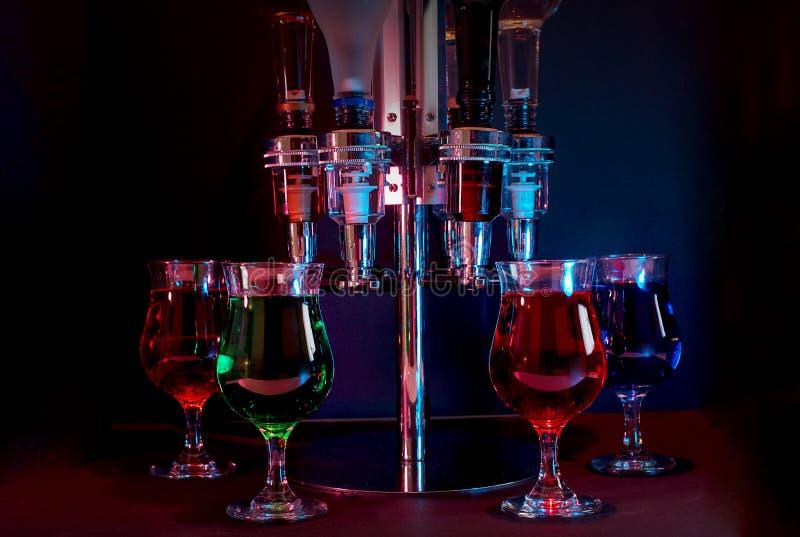 Diverses boissons avec le distributeur, éclairé à contre-jour dans une boîte de nuit image libre de droits