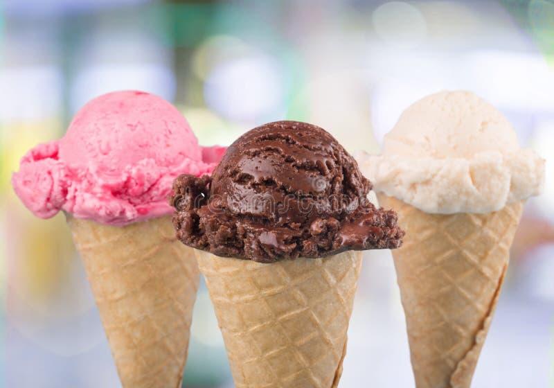 Diverses boules de crème glacée dans des cônes de gaufre sur brouillé image libre de droits