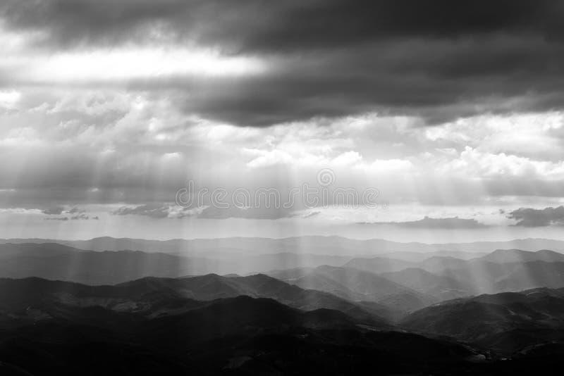 Diverses couches de collines et de montagnes avec la brume entre elles, avec des rayons du soleil sortant par les nuages photos libres de droits