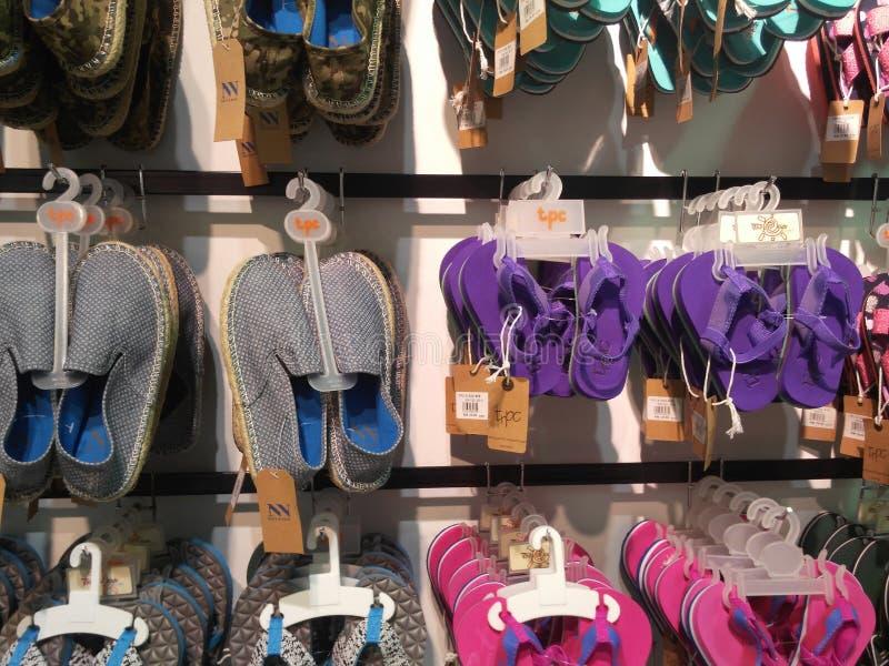 Diverses couleurs et tailles d'affichage de pantoufles, de sandale et de chaussures à vendre images libres de droits