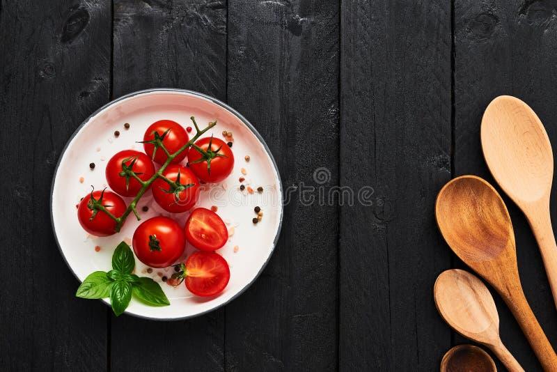 Diverses cuillères et tomates en bois dans un plat avec le sel de l'Himalaya photographie stock libre de droits
