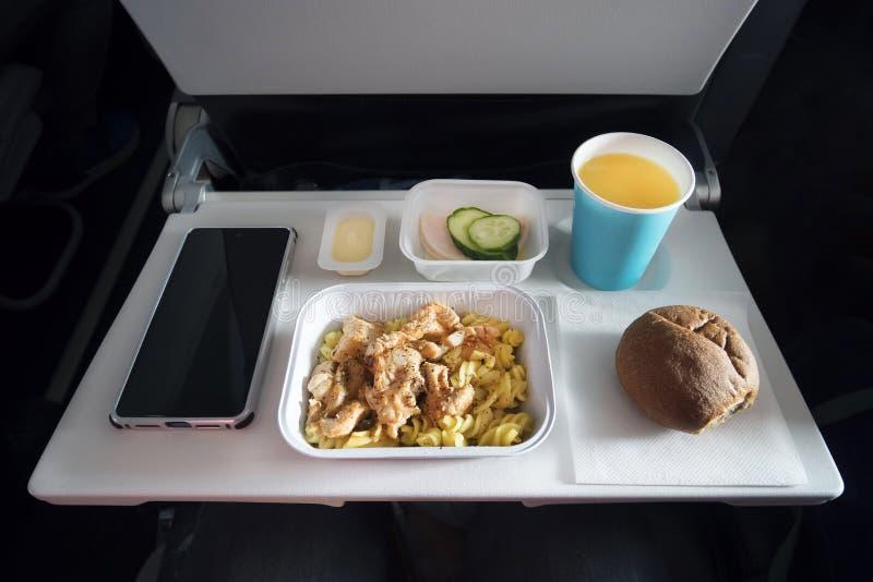 Diverses denrées alimentaires de classe économique et un smartphone passager avec écran blanc sur la table de pliage de l'aéronef photos libres de droits