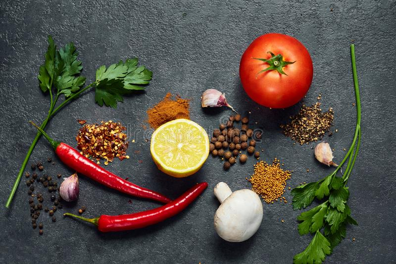 Diverses herbes et ?pices sur le fond noir Citron, poivre, sel, piment rouge, champignon, tomatoe, ail L'espace de copie de vue s photos stock