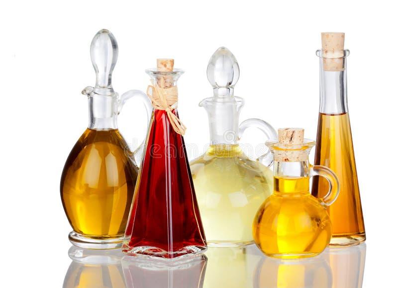 Diverses huiles de friture dans des carafes en verre avec la vraie réflexion photos stock