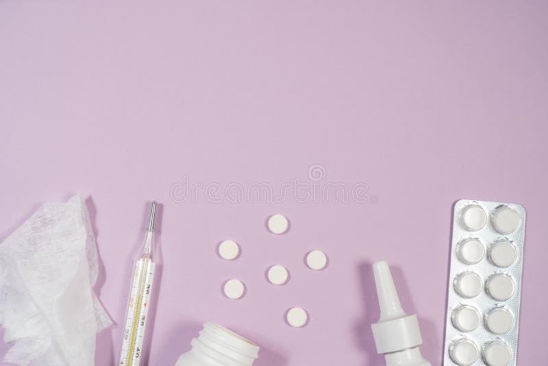 Diverses médecines, un thermomètre, pulvérisateurs d'un nez étouffant et une douleur dans une gorge sur un fond rose images libres de droits