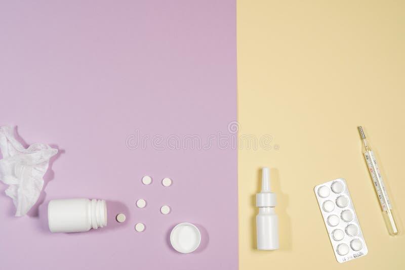Diverses médecines, un thermomètre, pulvérisateurs d'un nez étouffant et une douleur dans une gorge sur un fond rose image stock