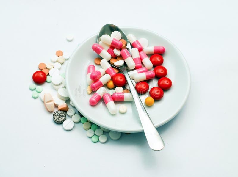 diverses pilules et cuillère dans un mage blanc de plat images stock