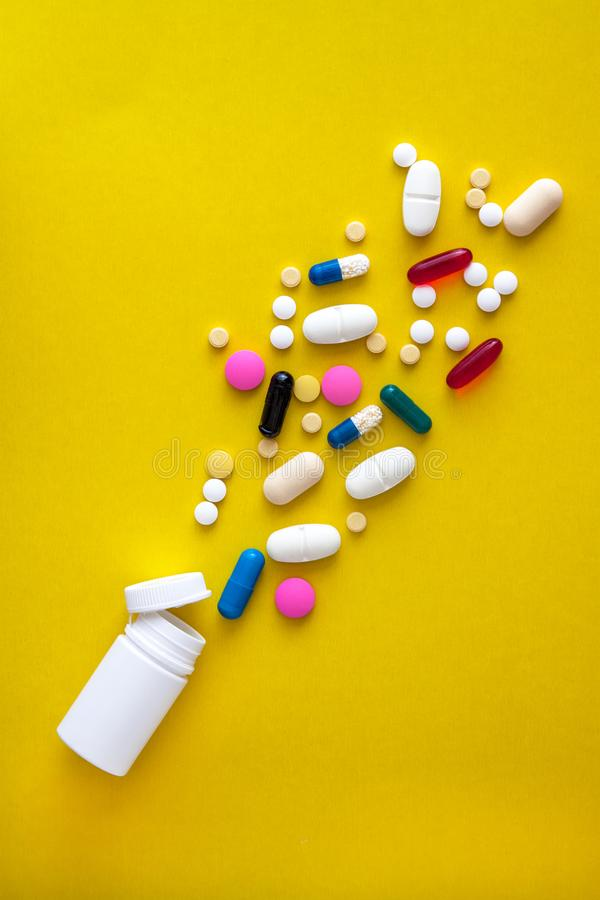 Diverses pilules et pilules médicinales se déversent du flacon sur fond jaune Pièce plate Espace de copie Tendance Le concept de photo libre de droits