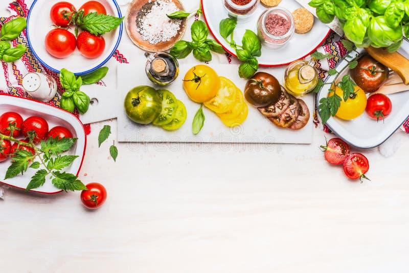 Diverses tomates colorées fraîches, préparation pour la salade saine sur le fond en bois blanc, vue supérieure photographie stock libre de droits