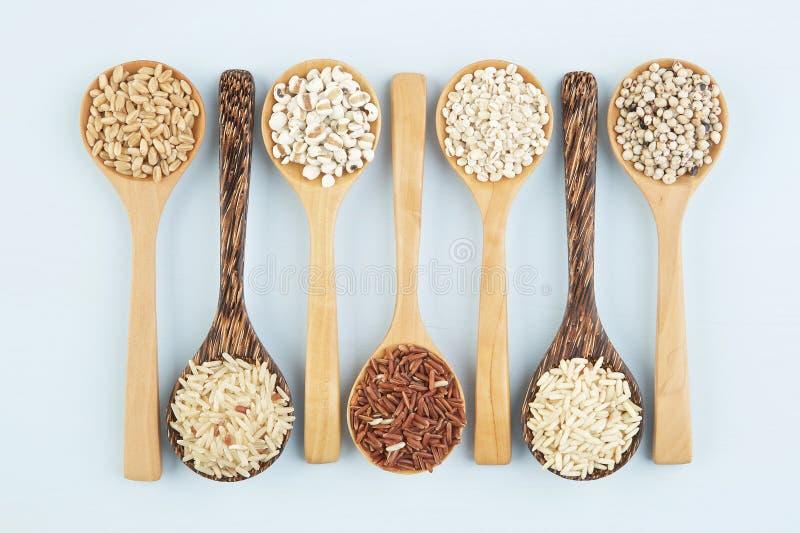 Diverses variétés de riz et de wholegrains dans la cuillère sur l'étiquette en bois photographie stock