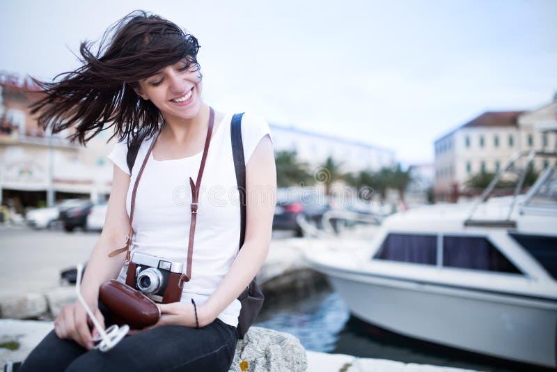Diversión de la mujer de la playa del verano que sostiene la cámara retra del vintage que ríe y que sonríe feliz durante viaje de foto de archivo libre de regalías