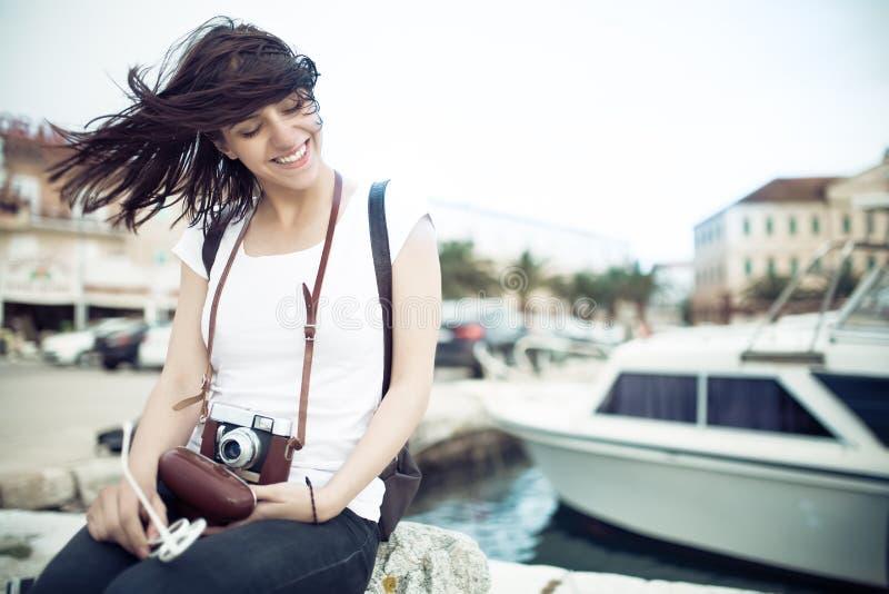 Diversión de la mujer de la playa del verano que sostiene la cámara retra del vintage que ríe y que sonríe feliz durante viaje de imagen de archivo