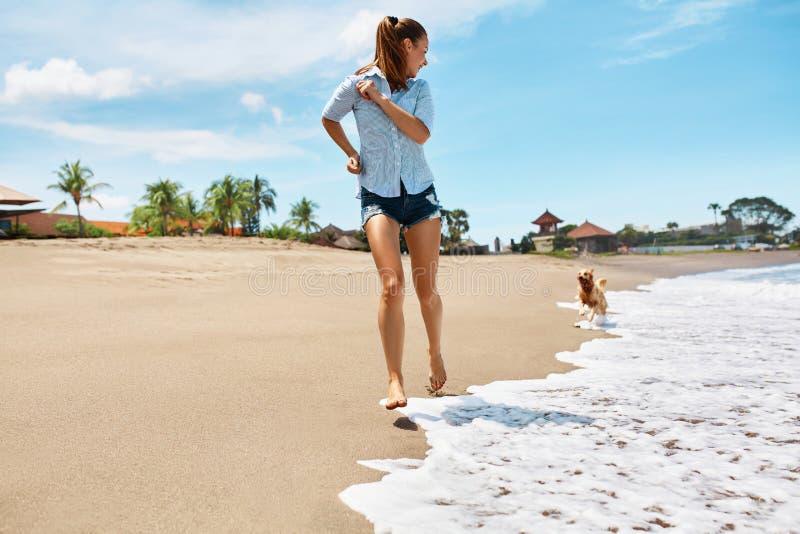 Diversión de la playa del verano Mujer que se ejecuta con el perro Vacaciones de los días de fiesta Verano fotografía de archivo libre de regalías