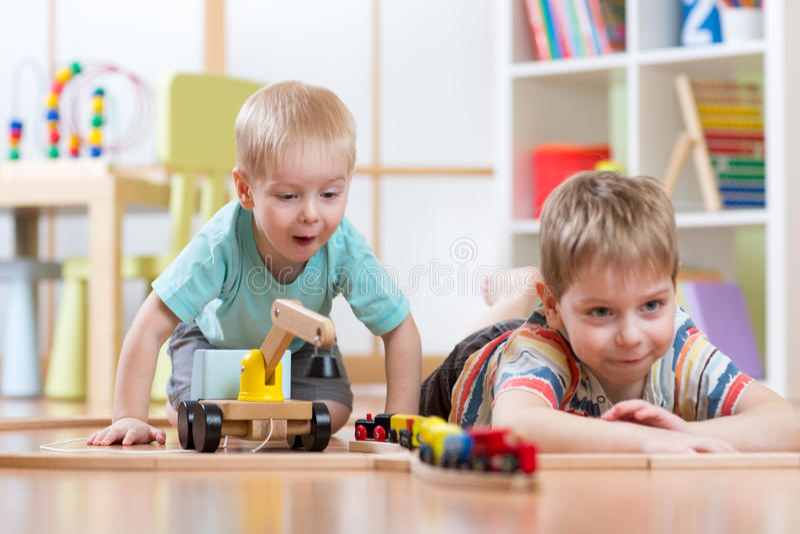 Diversión de los muchachos de los niños que juega con el ferrocarril de madera imágenes de archivo libres de regalías