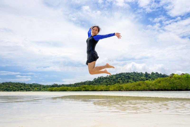 Diversión de salto de la muchacha adolescente asiática feliz en la playa imagen de archivo