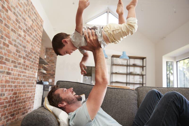 Diversión de And Son Having del padre que juega en Sofa Together imagen de archivo libre de regalías