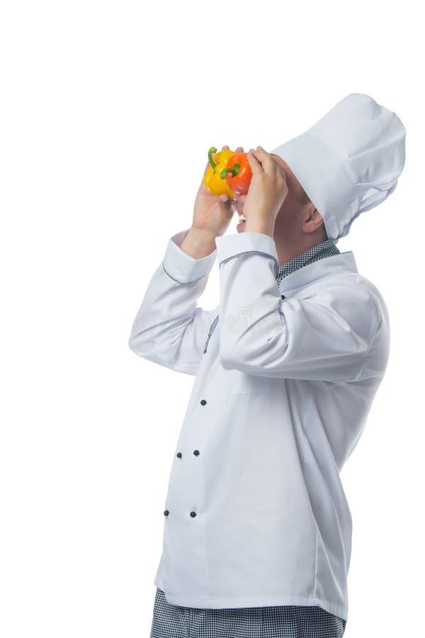 Diversión del cocinero con la pimienta dulce, mirando imagen de archivo