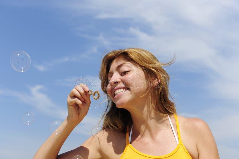 Diversión del verano: burbujas de jabón de la mujer que soplan al aire libre imagenes de archivo