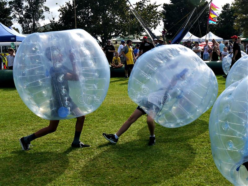 Diversión: dos muchachos que juegan las bolas del topetón zorbing imágenes de archivo libres de regalías