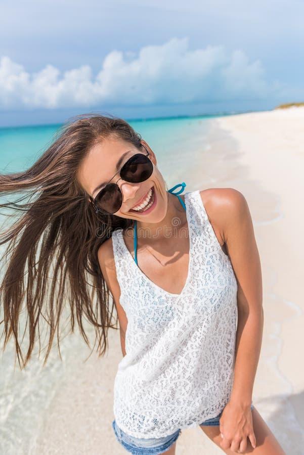 Diversión feliz de la playa de la mujer joven de las gafas de sol juguetona foto de archivo