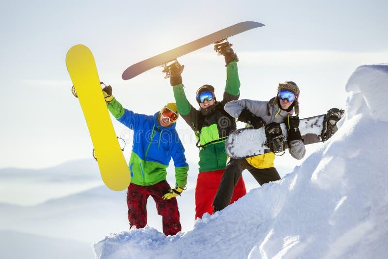 Diversión feliz de los snowboarders del grupo tres imagen de archivo