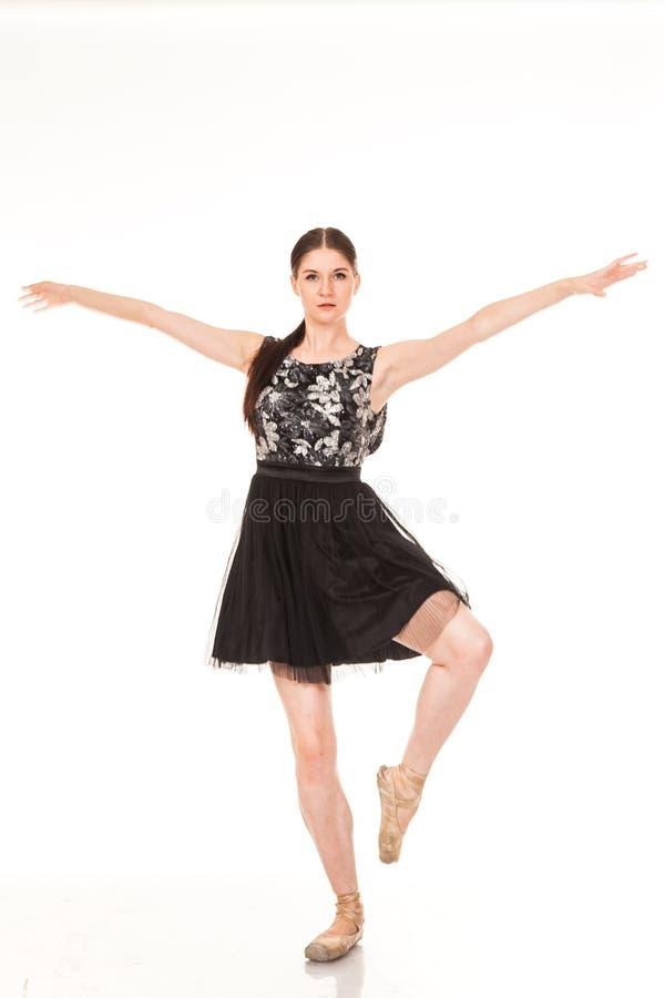 Diversión hermosa del baile de la muchacha en la cámara, presentando contra el fondo blanco fotos de archivo libres de regalías