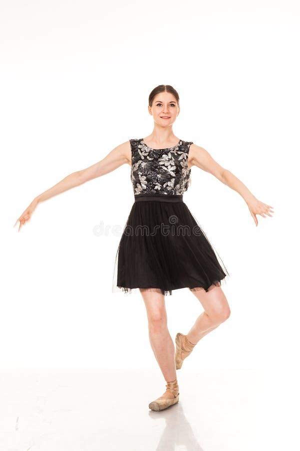 Diversión hermosa del baile de la muchacha en la cámara, presentando contra el fondo blanco foto de archivo
