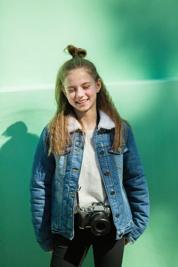 Diversión muchacha de doce años con los soportes de la cámara cerca de la pared verde imágenes de archivo libres de regalías