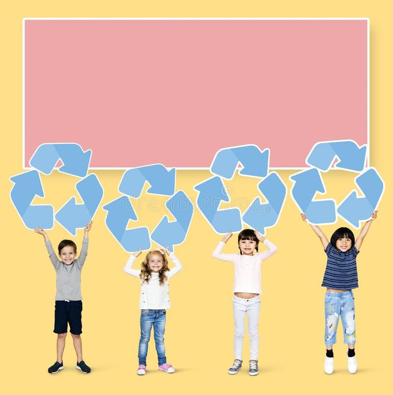 Diversi bambini che tengono riciclaggio delle icone immagini stock