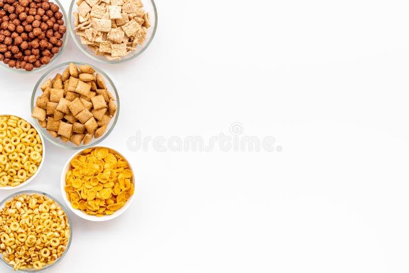 Diversi cereali in ciotole sul copyspace bianco di vista superiore del fondo fotografia stock libera da diritti