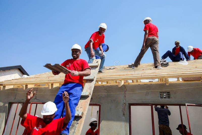 Diversi membri della comunità che costruiscono una casa di basso costo a Soweto immagine stock