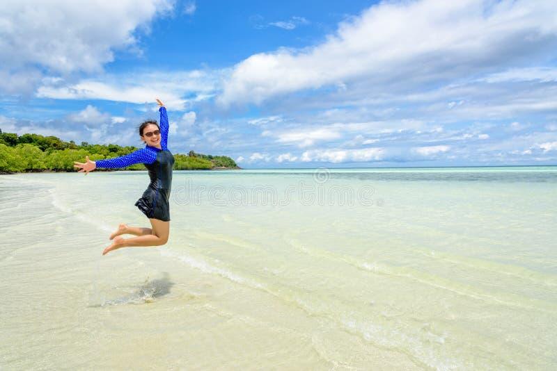 Diversi?n de salto de la muchacha adolescente asi?tica feliz en la playa imágenes de archivo libres de regalías